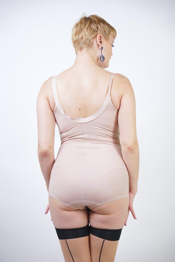 有摆在米黄葡萄酒紧身衣裤和性感的经典长袜的弯曲的身体的俏丽的白肤金发的短发减速火箭的妇女与缝在丝毫 免版税库存图片