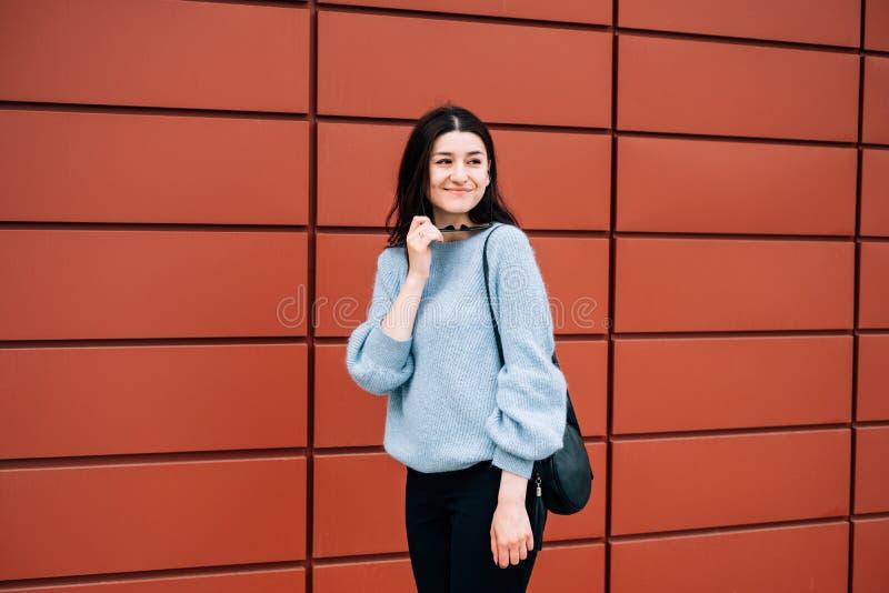 有摆在红色墙壁,街道样式,室外画象,行家女孩附近的黑发佩带的便服的美丽的少女  库存图片