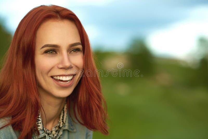 有摆在绿色领域的短的红色头发的笑的妇女 免版税图库摄影