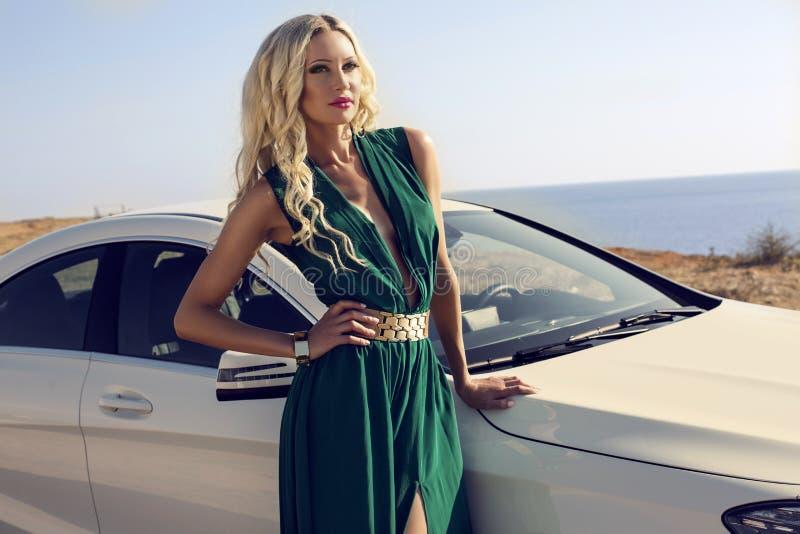 有摆在豪华汽车旁边的金发的性感的妇女 库存照片