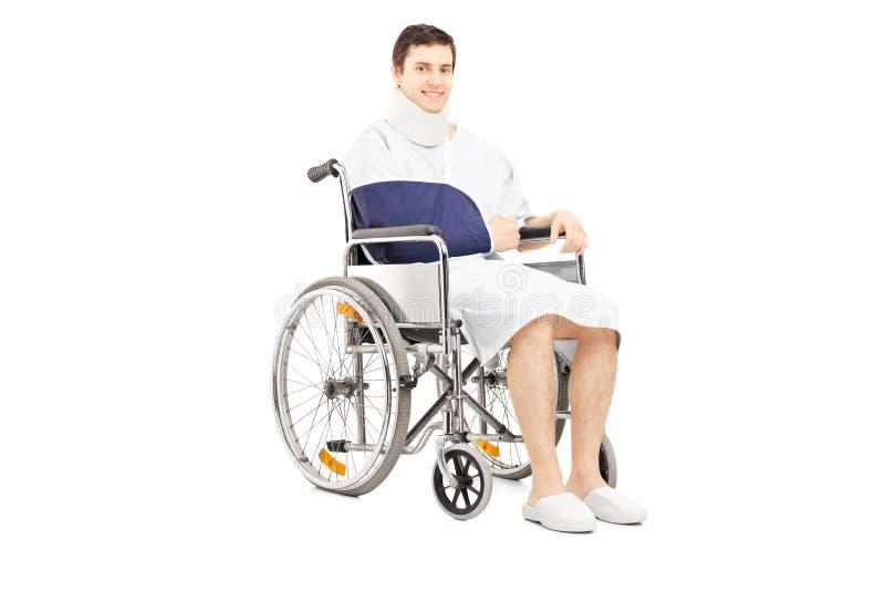 有摆在轮椅的断胳膊的残疾男性患者 免版税图库摄影