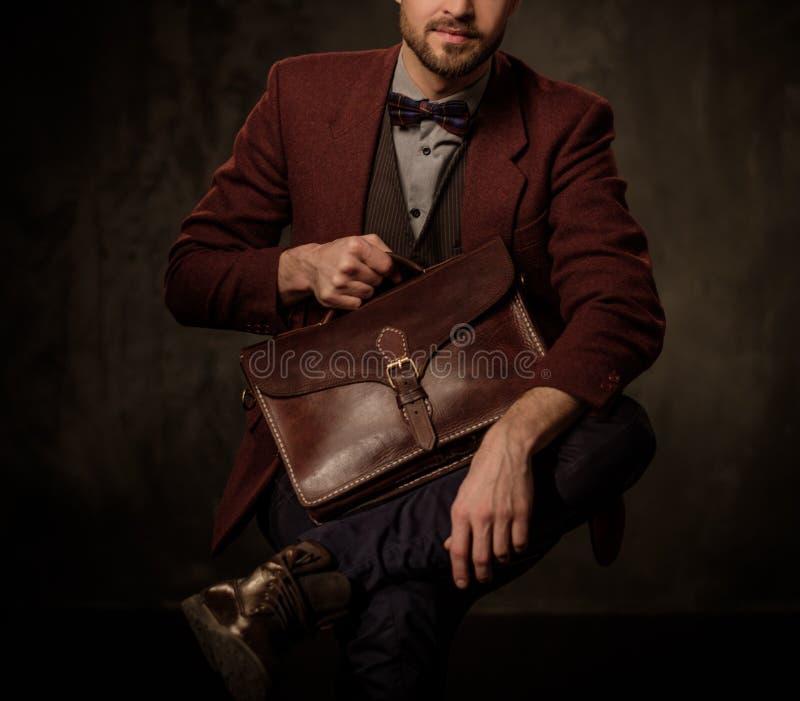 有摆在黑暗的背景的公文包的年轻英俊的古板的人 库存图片