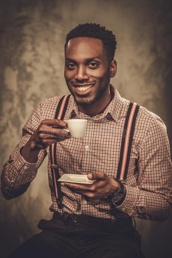 有摆在黑暗的背景的咖啡的时髦的黑人 图库摄影