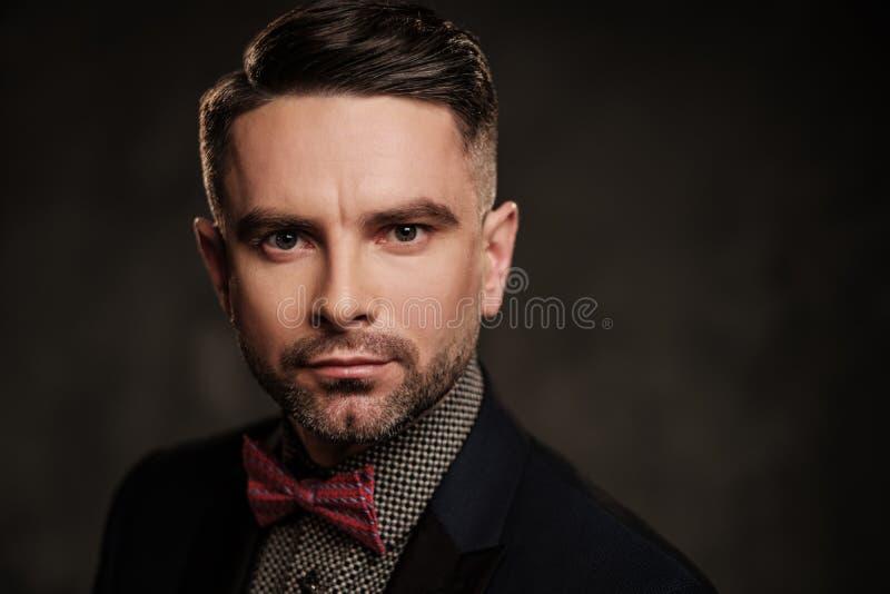 有摆在黑暗的背景的蝶形领结的穿着考究的时髦的年轻人 免版税库存图片