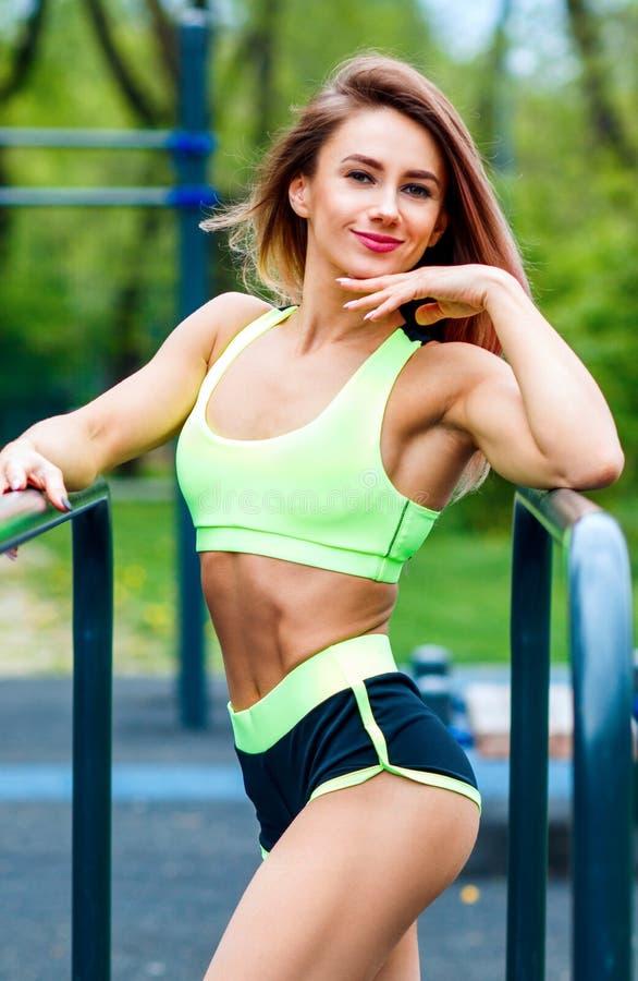 有摆在sportsground的完善的运动身体的运动的妇女 图库摄影