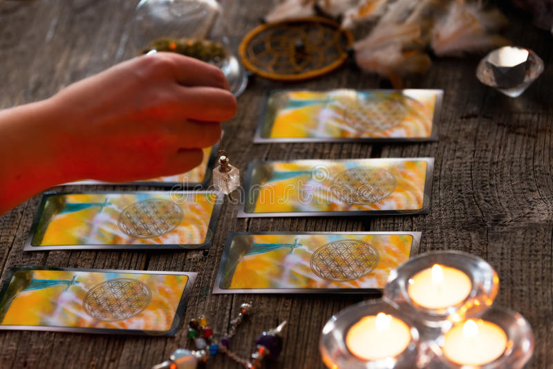 有摆锤的手在占卜用的纸牌 免版税库存图片