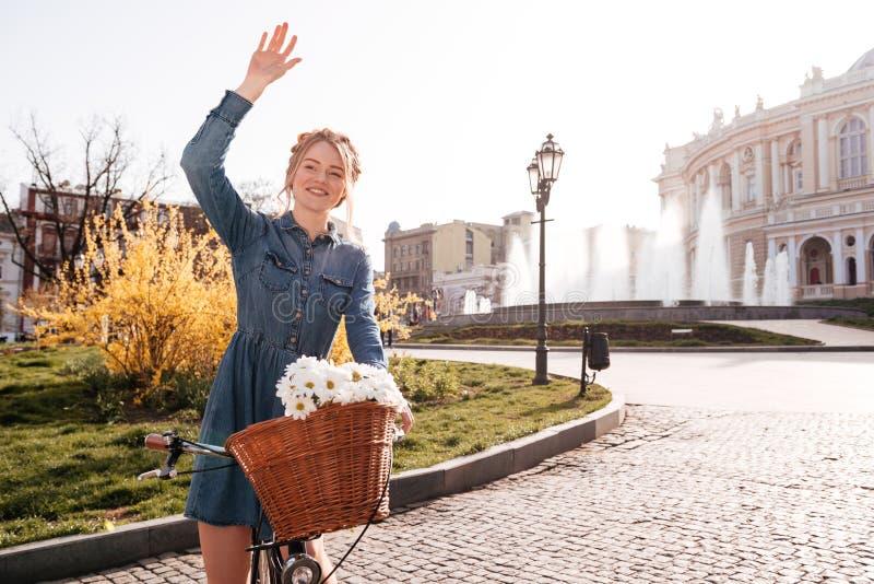 有摇她的在街道上的自行车的快乐的妇女手 库存照片