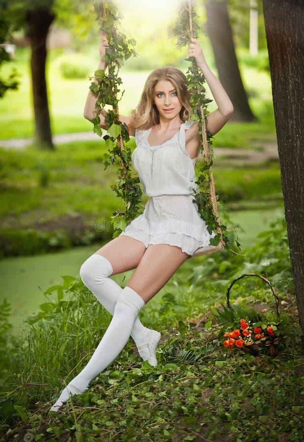 有摇摆在夏天庭院里的白色礼服的美丽的金发碧眼的女人 库存照片