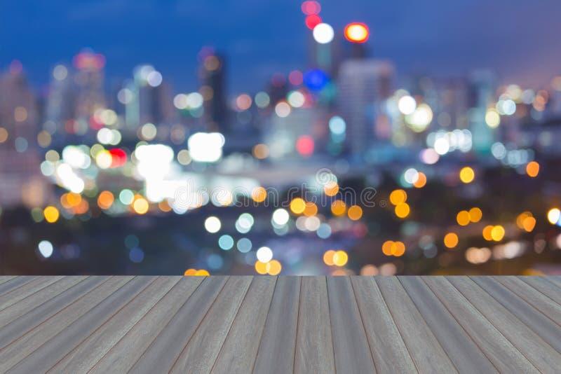 有摘要的木平台弄脏了bokeh城市光地平线,暮色backgroun 库存照片