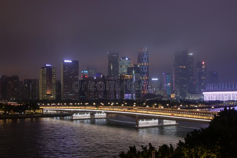 有摩天大楼的夜现代城市 在河的桥梁,城市大厦在晚上发光 在云彩的天空掩藏大厦 免版税库存图片