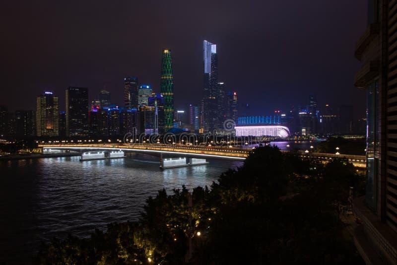 有摩天大楼的夜现代城市 在河的桥梁,城市大厦在晚上发光 在云彩的天空掩藏大厦 库存图片