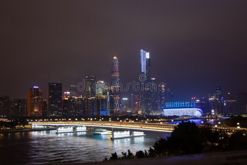有摩天大楼的夜现代城市 在河的桥梁,城市大厦在晚上发光 在云彩的天空掩藏大厦 图库摄影