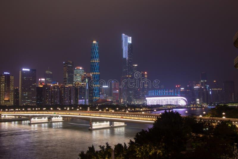 有摩天大楼的夜现代城市 在河的桥梁,城市大厦在晚上发光 在云彩的天空掩藏大厦 库存照片