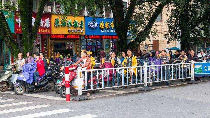 有摩托车和脚踏车的场面亚洲街道在行人穿越道附近的中止在桂林市中国 免版税库存照片