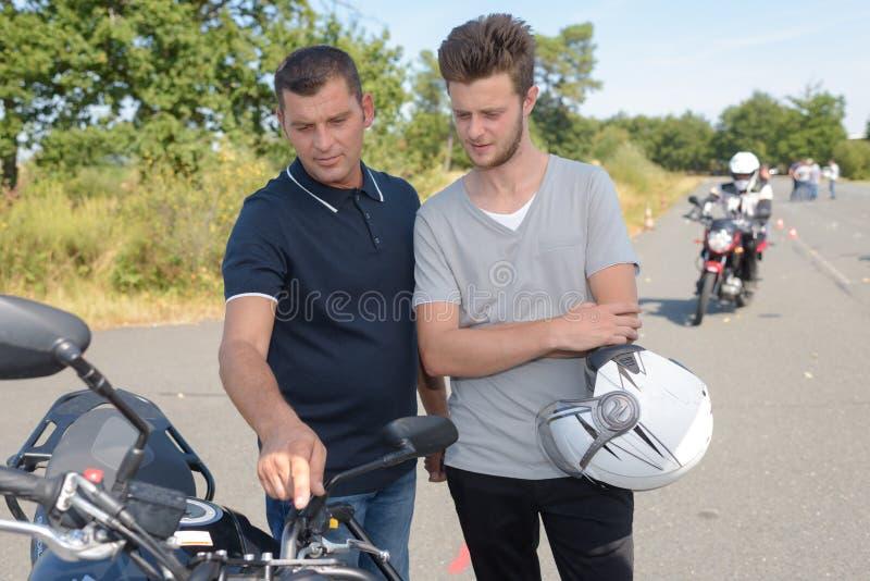 有摩托车和驾照的十几岁的男孩 免版税库存照片