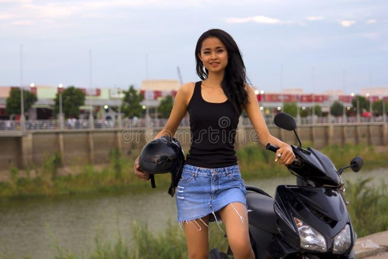 有摩托车的华美的亚裔女孩 库存图片