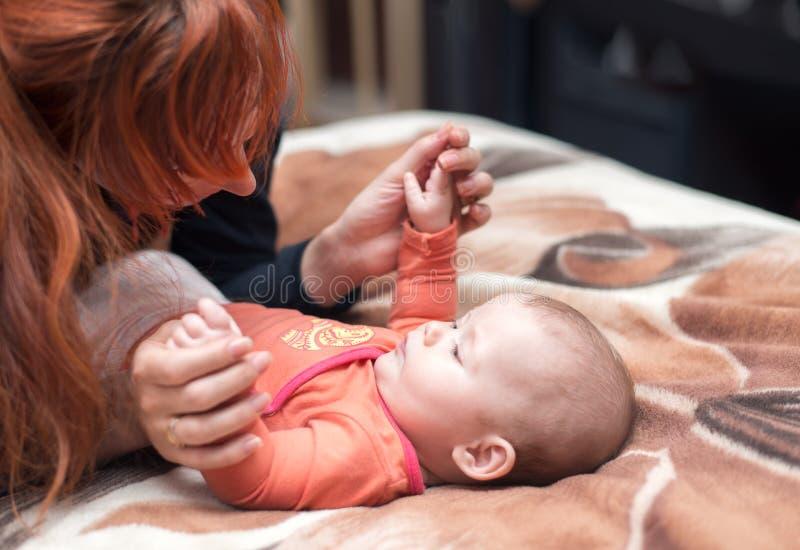 有播放孩子,愉快和微笑的红色头发的母亲 免版税库存图片