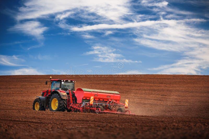 有播种庄稼的拖拉机的农夫在领域 图库摄影
