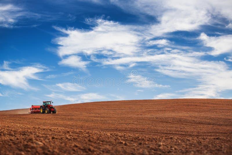 有播种庄稼的拖拉机的农夫在领域 库存图片