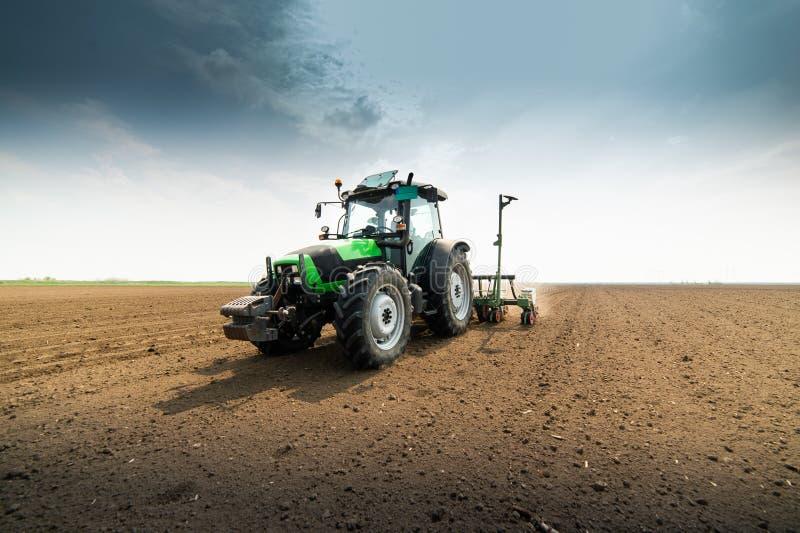 有播种的拖拉机的农夫播种庄稼在农业领域 库存照片