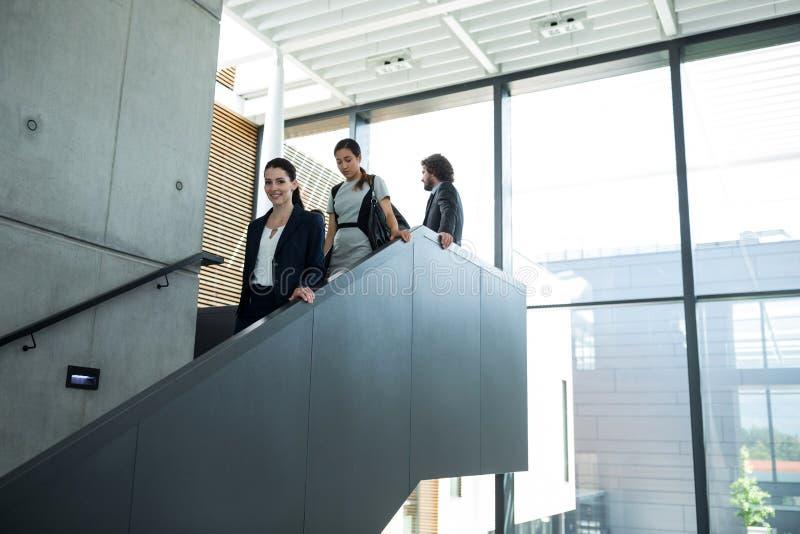 有攀登下来台阶的同事的确信的女实业家 免版税库存图片