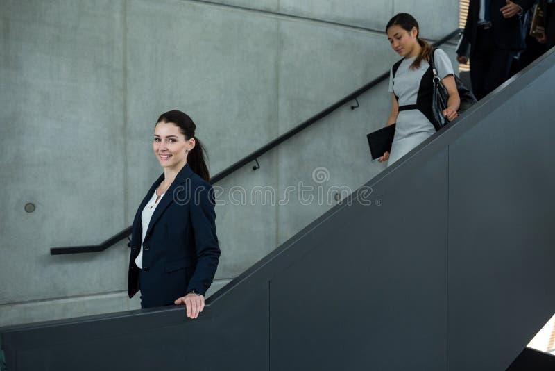 有攀登下来台阶的同事的确信的女实业家 免版税图库摄影