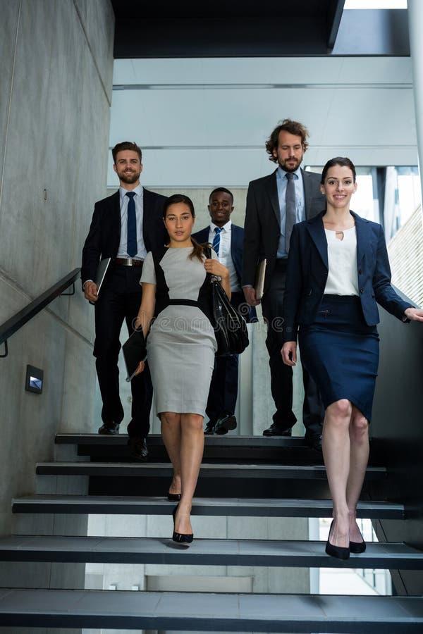 有攀登下来台阶的同事的确信的女实业家 库存图片