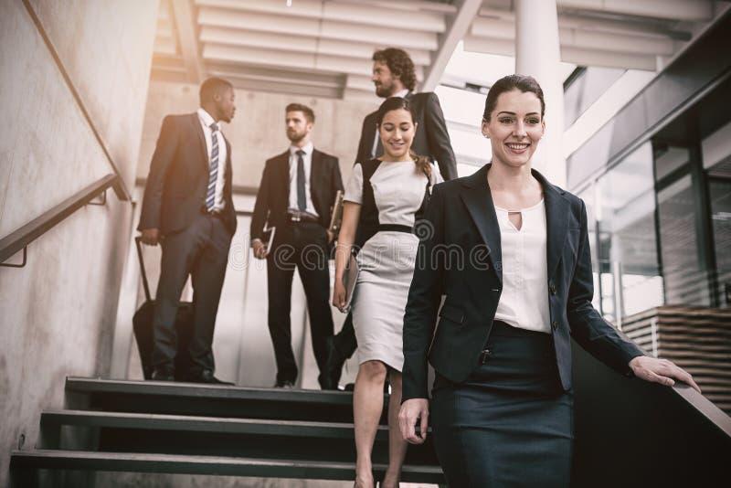 有攀登下来台阶的同事的确信的女实业家 免版税库存照片
