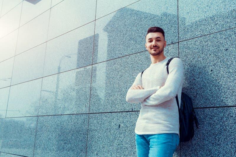 有支持墙壁的背包的阿拉伯学生外面 年轻人等待的groupmates 免版税库存照片