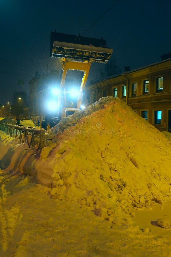 有收集在随风飘飞的雪的桶的推土机雪在路一边 图库摄影
