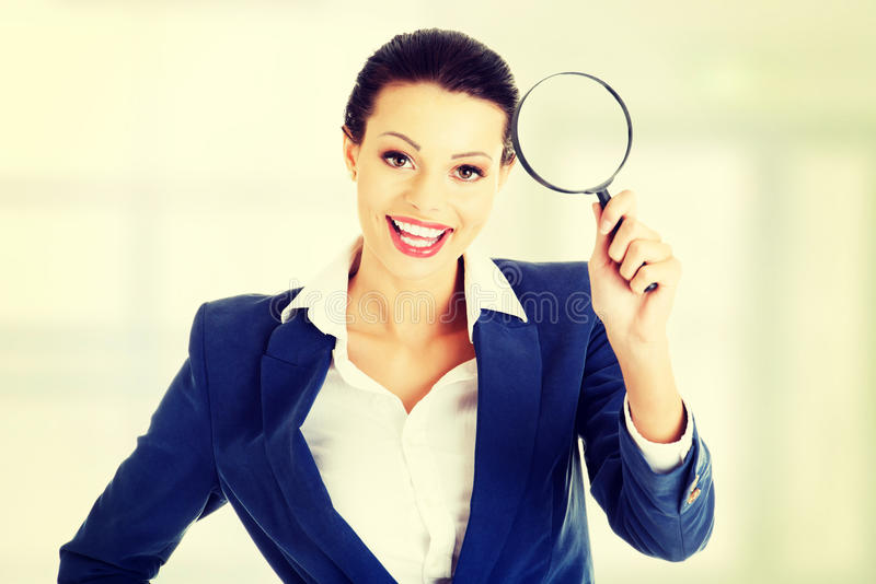 有放大器玻璃的女实业家 免版税库存图片