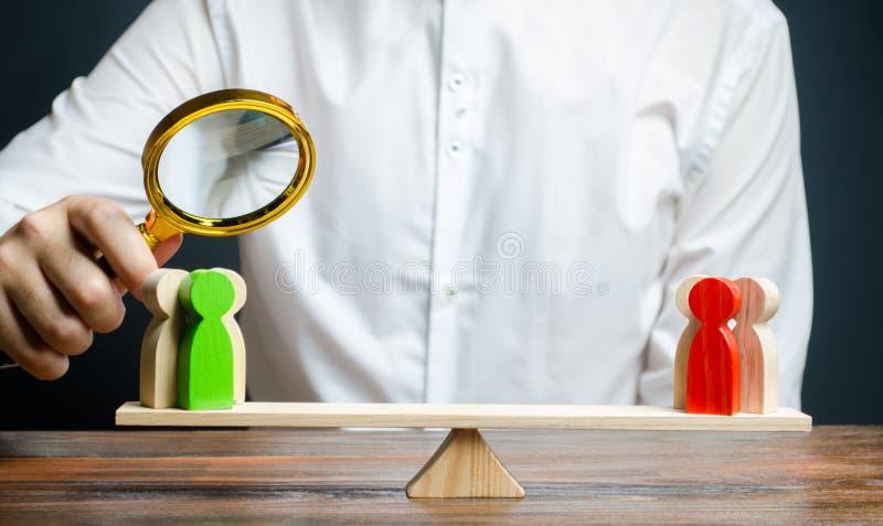 有放大镜的一个人注视着在等级的敌手红色和绿色图小组 解决冲突 免版税库存图片