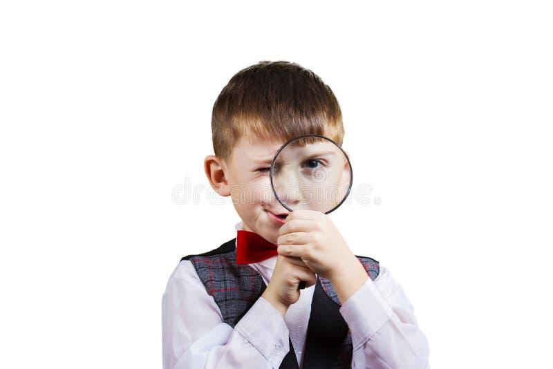 有放大镜的好奇探索的小男孩 免版税库存照片