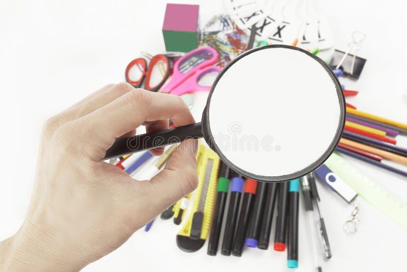 有放大镜的手在学校用品 与拷贝空间的照片 免版税库存照片
