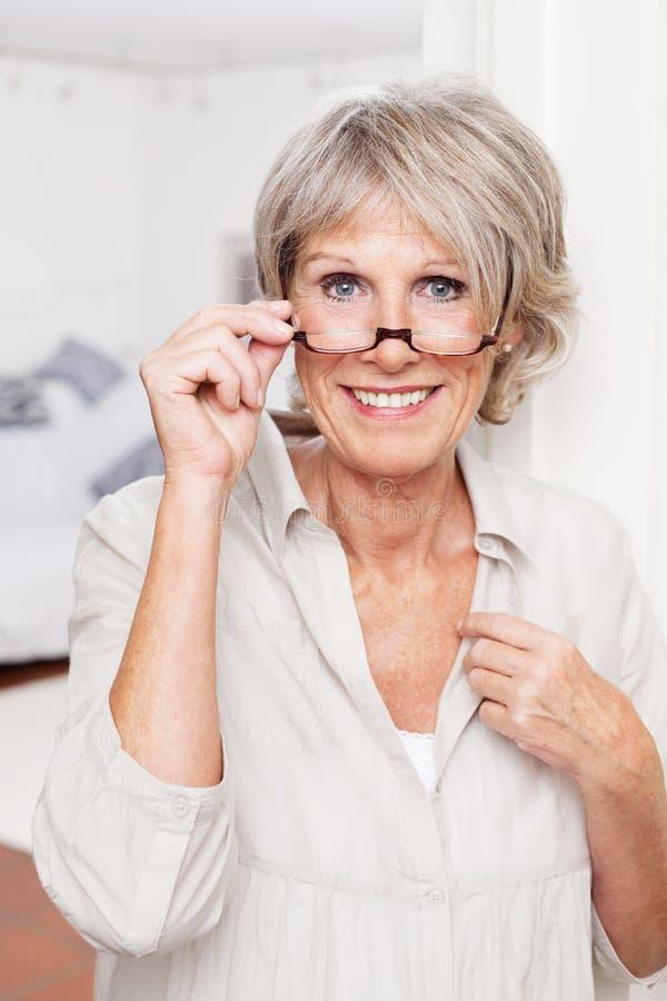 有放大镜的年长夫人 免版税库存图片