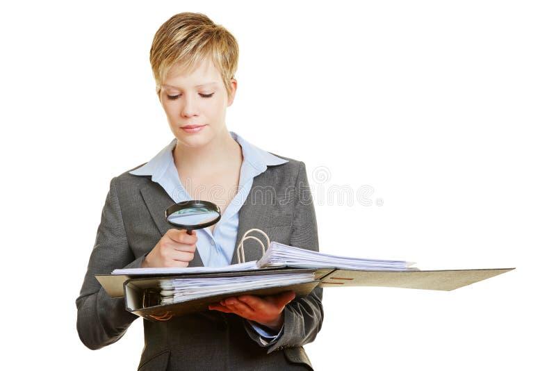 有放大镜读书合同的妇女 免版税库存图片
