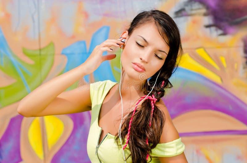 有放松和听到音乐的耳机的美丽的少妇。 免版税库存图片