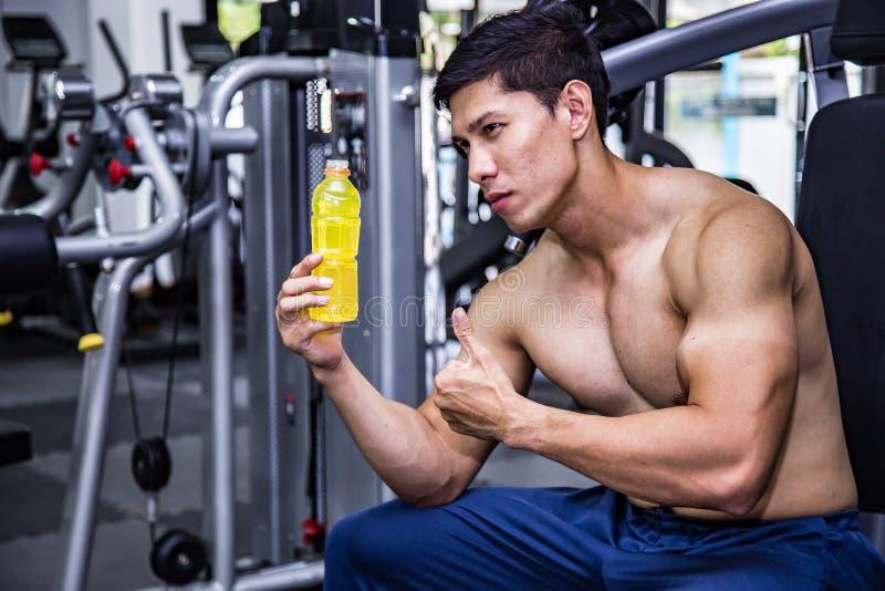 有放松和喝在健身房的能量饮料的亚裔适合的人 体育和fittness概念 并且亚洲英俊的肌肉疲乏 免版税库存照片