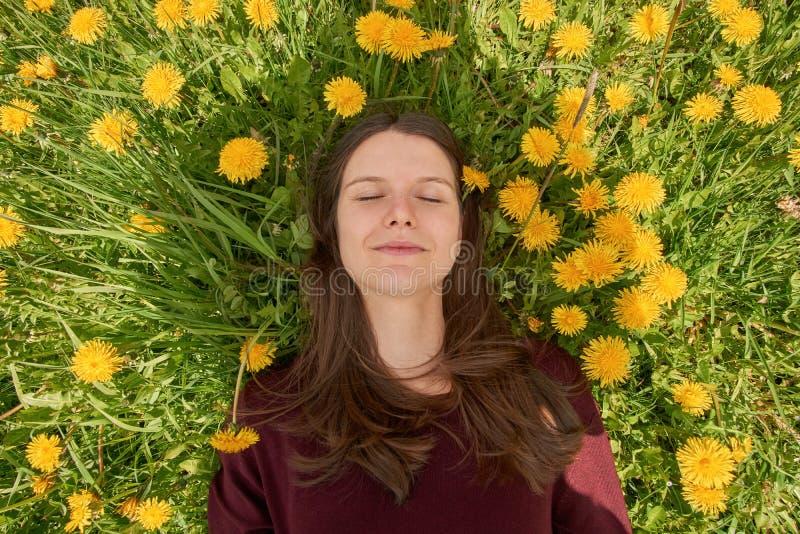 有放松在一个草甸的闭合的眼睛的微笑的少妇用许多蒲公英在春天太阳 上面下来观看 免版税库存照片