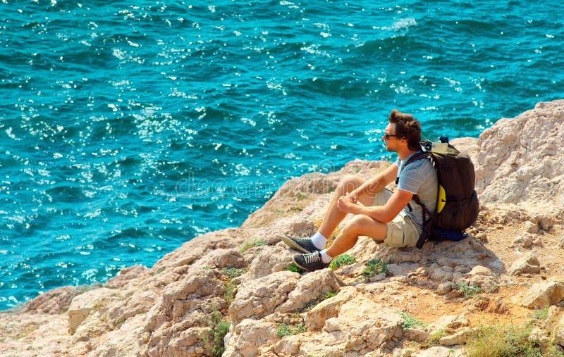 有放松在与蓝色海的岩石峭壁的背包的年轻人背景的 图库摄影