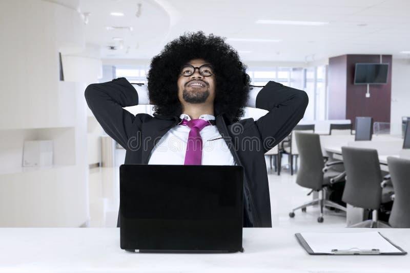 有放松在办公室的膝上型计算机的非裔美国人 免版税图库摄影