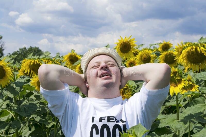 有放松在向日葵领域的唐氏综合症的愉快的年轻人 库存图片