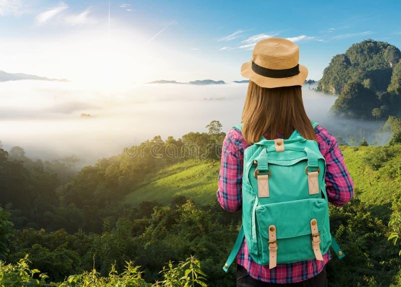 有放松在山顶部和享受谷的看法背包的远足者 库存图片