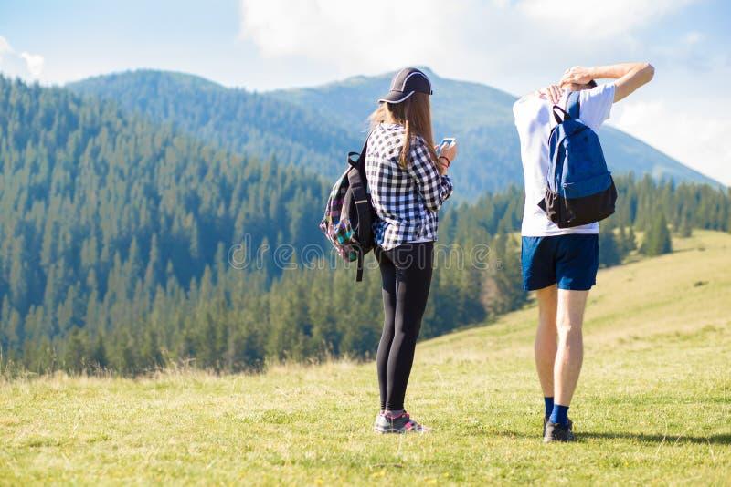 有放松在山顶部和享受谷的美丽的景色背包的徒步旅行者, 免版税图库摄影