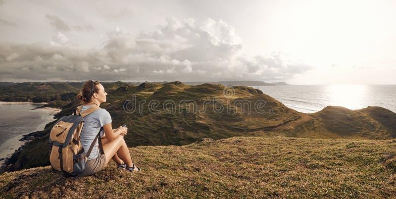 有放松在山顶部和享用平底锅的背包的远足者 免版税库存图片