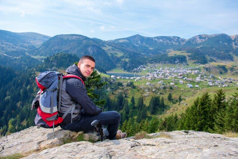 有放松在山顶部的背包的年轻男性徒步旅行者在镇静夏日期间 免版税库存图片