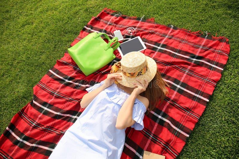 有放松在格子花呢披肩的帽子的年轻女人户外 免版税库存照片