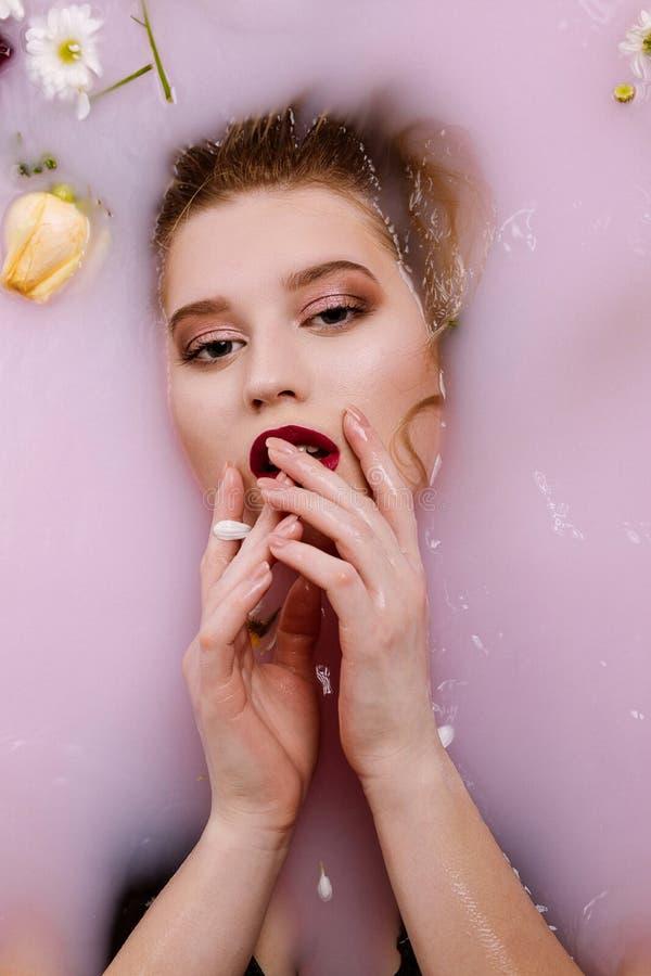 有放松在浴的完善的构成的诱人的白肤金发的女孩用牛奶和花 图库摄影