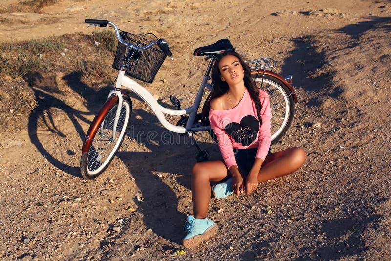 有放松在海滩的自行车的俏丽的浅黑肤色的男人 免版税图库摄影