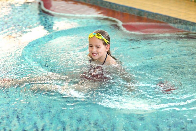 有风镜的愉快的女孩在游泳池 免版税库存照片